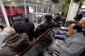 Iranian investors monitor an electronic board at the Tehran Stock Exchange